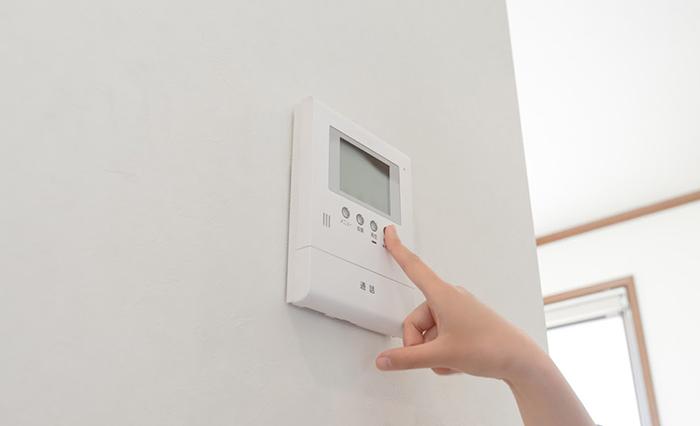 エアコンのスイッチを押している